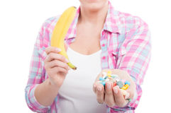 Woman holding banana and tablet pills. As alternative nutrients concept on white background Royalty Free Stock Photos