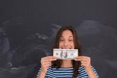 Woman holding a banknote in front of chalk drawing board. Portrait of a young woman holding a banknote in front of chalk drawing board Stock Photo