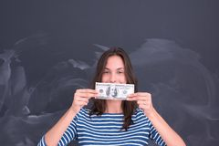 Woman holding a banknote in front of chalk drawing board Stock Photo