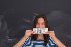 Woman holding a banknote in front of chalk drawing board Stock Images