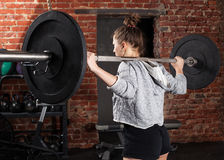 Woman holding a barbell on his shoulders royalty free stock image