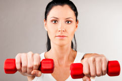 Woman is holding barbells. Sporty woman is holding two red barbells on grey background and looking at camera Stock Photo
