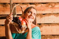 Woman holding a basket of apples and grapes Stock Images