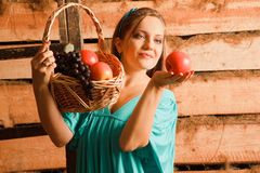 Woman holding a basket of apples and grapes Royalty Free Stock Photos
