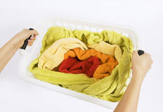 Woman holding a basket with color laundry to wash. Woman holding a white plastic basket with colorful laundry to wash Royalty Free Stock Photo