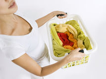 Woman holding a basket with colorful laundry to wa. Woman holding a white plastic basket with colorful laundry to wash Stock Photo