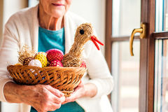 Woman holding basket with Easter eggs and straw hen Stock Photography