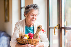 Woman holding basket with Easter eggs and straw hen Stock Photo