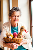 Woman holding basket with Easter eggs and straw hen Stock Images