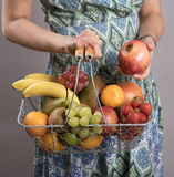 WOMAN HOLDING A BASKET OF FRESH FRUIT Royalty Free Stock Photography