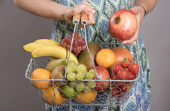 WOMAN HOLDING A BASKET OF FRESH FRUIT Stock Images