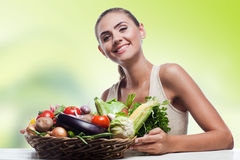 Woman holding basket with vegetable. Happy young woman holding basket with vegetable. Concept vegetarian dieting - healthy food Royalty Free Stock Photos