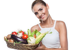 Woman holding basket with vegetable. Happy young woman holding basket with vegetable. Concept vegetarian dieting - healthy food Royalty Free Stock Photo