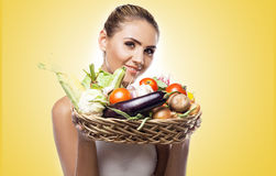 Woman holding basket with vegetable. Concept vegetar. Happy young woman holding basket with vegetable. Concept vegetarian dieting - healthy food Stock Photography