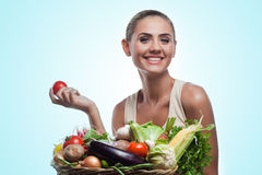 Woman holding basket with vegetable. Concept vegetarian dieting. Happy young woman holding basket with vegetable. Concept vegetarian dieting - healthy food Stock Images