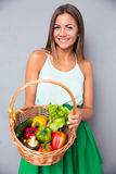 Woman holding basket with vegetables Stock Images