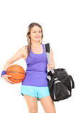 Woman holding basketball and a sports bag Royalty Free Stock Photo