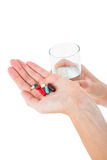 Woman holding batch of pills and glass of water Stock Images