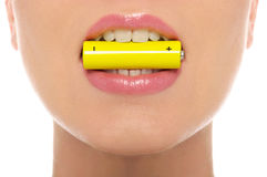 Woman holding battery in his mouth royalty free stock image