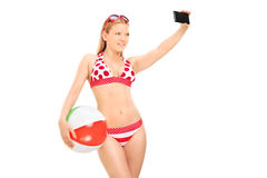 Woman holding a beach ball and taking selfie Stock Images
