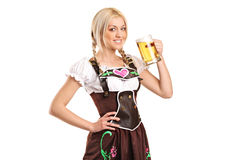 Woman holding a beer glass. A woman wearing a traditional costume and holding a beer glass isolated on white background royalty free stock images