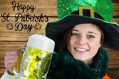 Woman holding beer next to st patricks day greeting. On wooden background Royalty Free Stock Photography