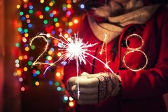 Woman holding sparkles on his hand on bokeh lights background. New Year's Eve concept. 2018 written with sparkle fireworks. Woman holding bengal lights stock photography