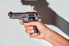 Woman holding beretta gun in her hand and aiming Royalty Free Stock Images