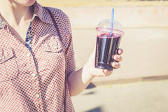 Woman holding berry drink in plastic cup with straw Royalty Free Stock Image