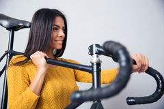 Woman holding bicycle on shoulder Stock Image