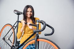 Woman holding bicycle on shoulder Royalty Free Stock Photos