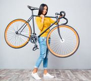 Woman holding bicycle on shoulder Stock Images