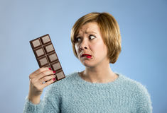 Woman holding big chocolate bar with mouth stains and guilty face expression in sugar addiction Royalty Free Stock Photos