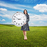 Woman holding big clock and looking Stock Photography