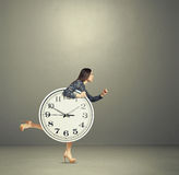 Woman holding big clock and running Royalty Free Stock Image