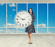 Woman holding big clock, smiling Royalty Free Stock Images