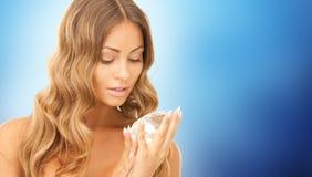 Woman holding big diamond over blue background Stock Image