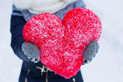 Woman is holding big heartshape pillow outdoors in winter. Stock Photo
