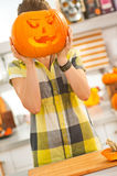 Woman holding a big Jack-O-Lantern pumpkin in front of head Stock Image