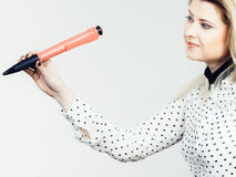 Woman holding big oversized pen Royalty Free Stock Photography