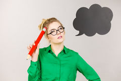 Woman holding big oversized pencil thinking Stock Photography