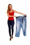 Woman holding big pants. Royalty Free Stock Photos