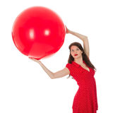 Woman holding big red balloon above her head Stock Image