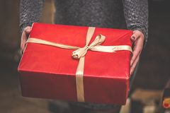 Woman holding a big red gift box. Christmas or valentines day concept. Toned and selective focus.  Royalty Free Stock Image
