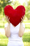 Woman holding big red heart before her face Stock Photos