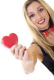 Woman holding a big red heart and smiling. Portrait of a young cheerful blond woman holding a big red heart and smiling. Isolated on white Royalty Free Stock Photography