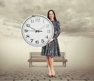 Woman holding big white clock Royalty Free Stock Images