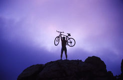 Woman holding bike overhead Stock Image