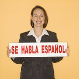 Woman holding bilingual sign Royalty Free Stock Photo
