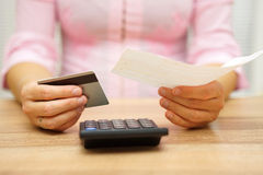 Woman is holding bill and credit card in hands and calculating stock images